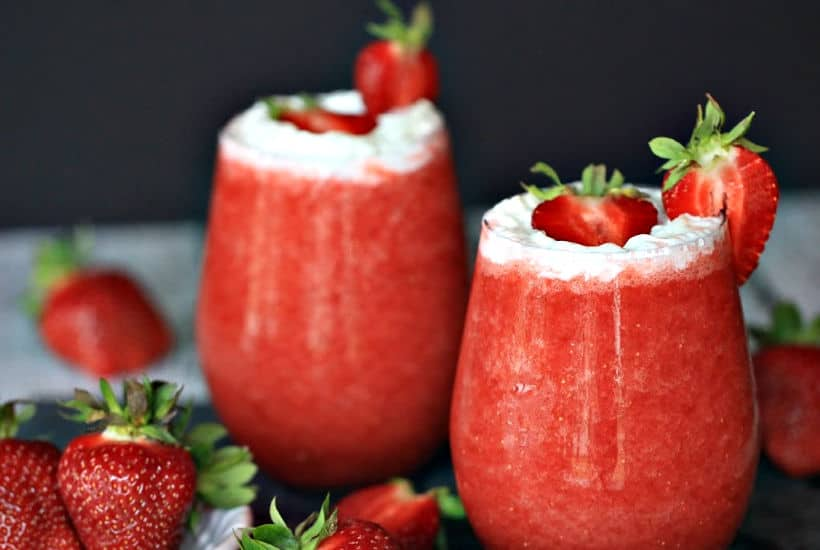Cheers to Strawberry season. With just a few simple ingredients, you can make your own Strawberry Shortcake Daiquiris at home. Skip the mix and make fresh strawberry daiquiris at home using this easy recipe. It's the perfect slushy cocktail for cooling down in warmer weather! #strawberrydaiquiri #cocktails #slush