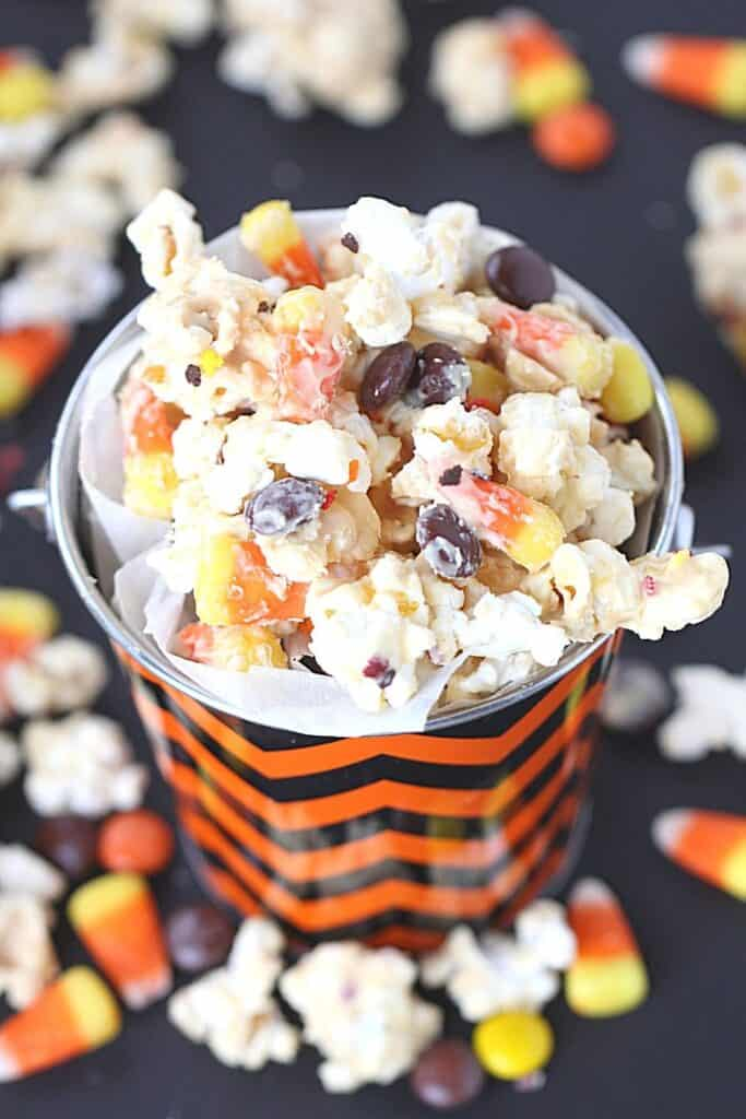 Scare up some Halloween fun with this Candy Corn Popcorn. It's the perfect Halloween Snack to enjoy during the fall season. This is an easy Halloween snack recipe. One of my favorite snacks during the Halloween season is this Candy Corn Popcorn. It is loaded with lots of sweet candy corn, melted chocolate and chocolate candy. What's not to love?
