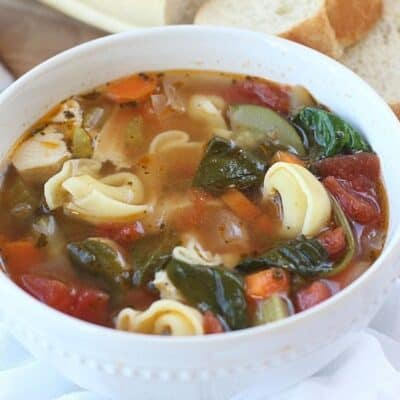 This classic Tuscan Chicken Soup will warm you up on a cold winter's day! This easy soup recipe is filled with hearty vegetables, chicken and tortellini. This Italian-style chicken soup is easy to prepare and is filled with spinach too. It can be easily prepared in a slow cooker, making it a delicious slow cooker chicken soup or an easy Instant Pot Soup recipe.