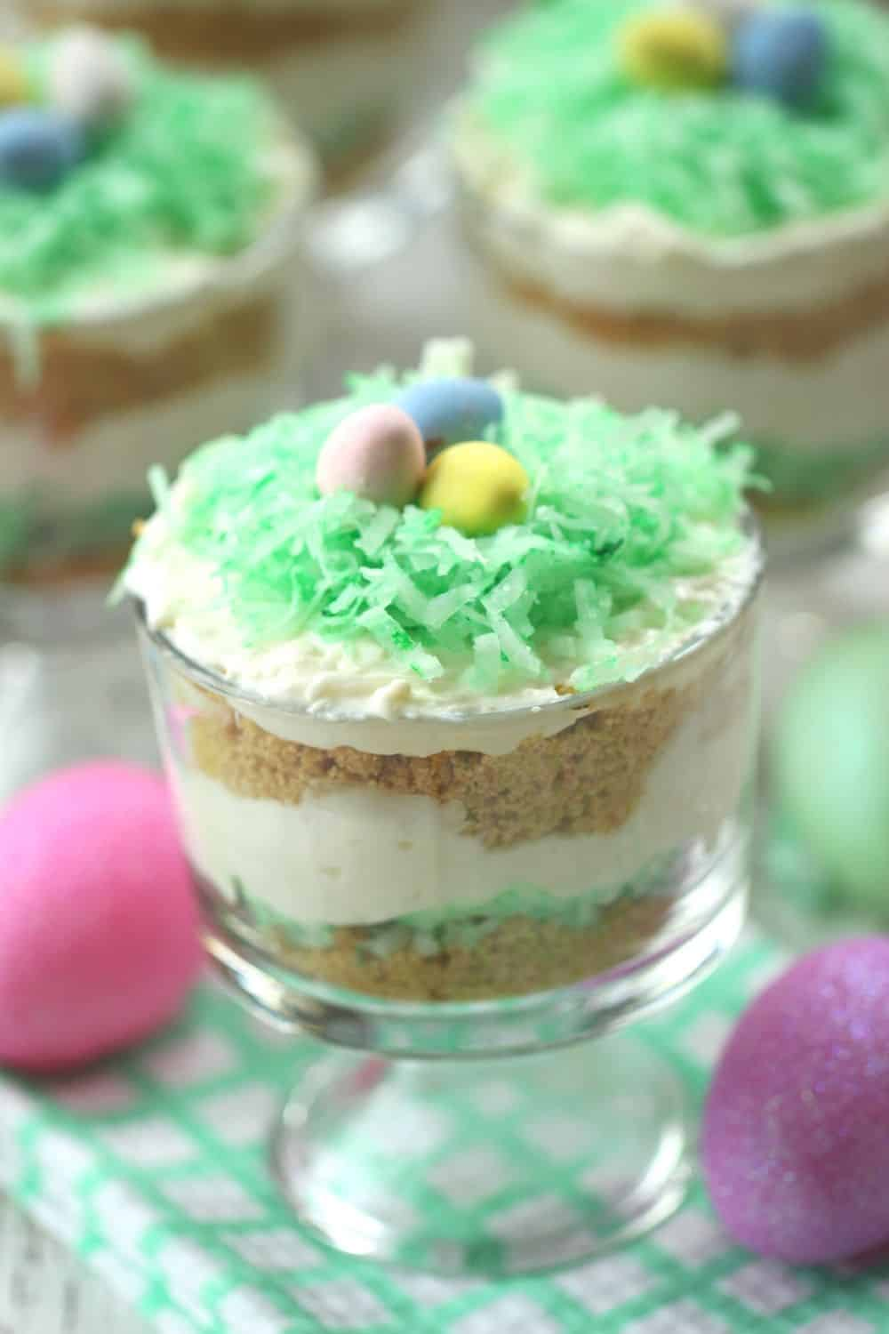 These colorful No Bake Coconut Cheesecake Parfaits are a sweet way to welcome spring. They are a perfect Easter dessert recipe for your holiday celebration. This no-bake dessert recipe can be served in mason jars or parfait dishes. This easy holiday dessert recipe can also be made ahead of time. #nobakedessert #masonjarrecipe #easterdessert #cuteeasterdessert