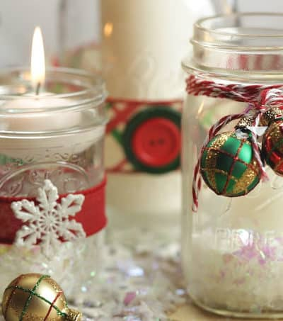 Set the moor and create a welcoming tablescape this Christmas with these pretty Mason Jar Christmas Candles.  #masonjar #masonjarcrafts #ChristmasDecorations #Christmasdecor #Christmascrafts #Xmasdecorations #Xmascrafts