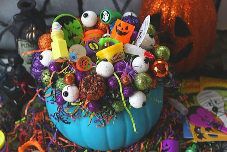 This DIY Teal Pumpkin Treat Holder is all treats and no tricks. Trick or Treaters will love this teal pumpkin filled with non-candy treats. This Halloween craft project is made using a craft pumpkin, styrofoam balls and crinkle paper. It's a perfect way to provide allergy-friendly treats to your little ghouls and goblins. #tealpumpkin #halloweencraft #pumpkincarving