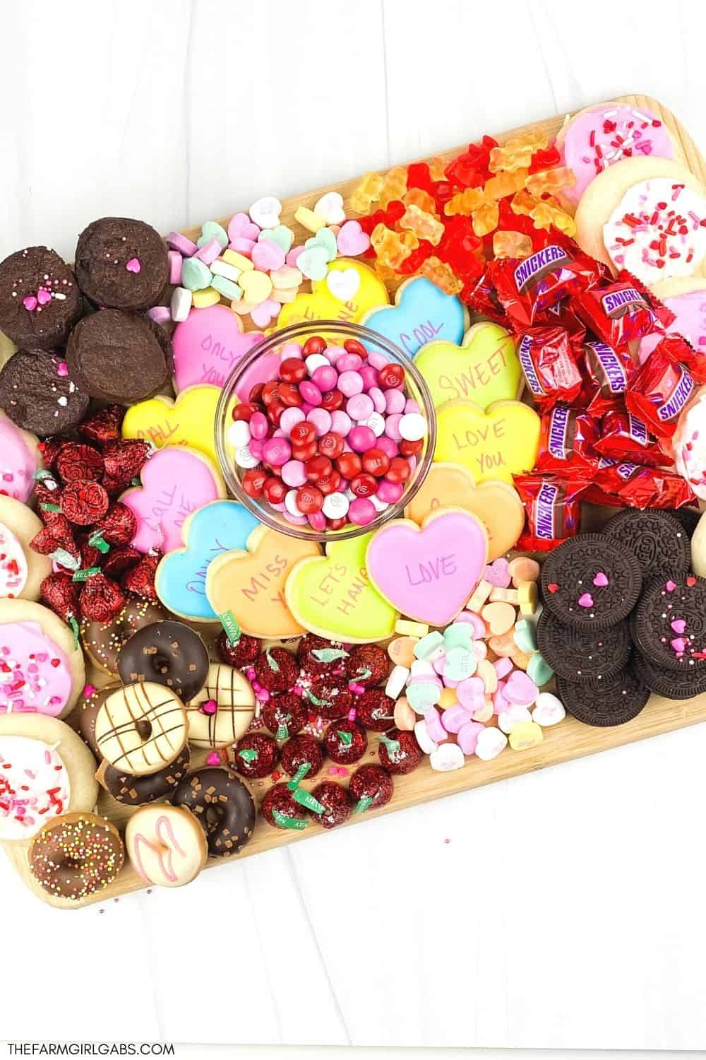 Kids and adults will love eating this Valentine's Day Dessert Board. Find out how to make an easy dessert board for Valentine's day filled with candy and treats. This Valentine's Day charcuterie board is great to make for a party or tailor to any special holiday. Learn how to make a charcuterie board for your next party or gathering. Kids and adults will enjoy this easy dessert board filled with your favorite candies and sweet treats. Read more to find out how to make a holiday dessert board.
